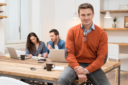 team success: Successful businessman smiling and looking at camera with other workers sitting in background
