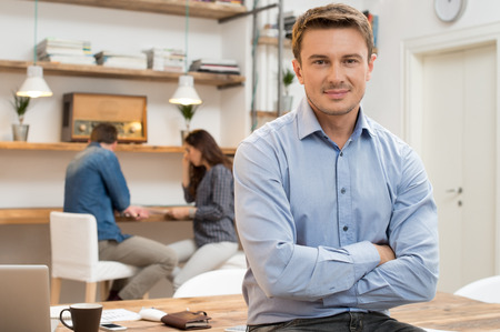 man relax: Portrait of smiling young businessman with armcrossed looking at camera in office