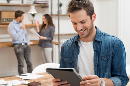 Nahaufnahme der junge Geschäftsmann mit Tablette mit Arbeitnehmern im Hintergrund