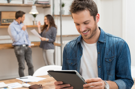 typing: Primer plano de hombre de negocios joven que usa la tableta con los trabajadores en el fondo Foto de archivo