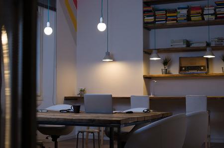 biblioteca: Computadora portátil en el escritorio con sillas vacías en la oficina moderna Foto de archivo