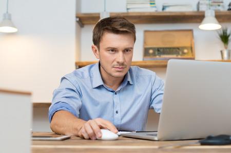 オフィスでラップトップを使用して青年実業家の肖像画