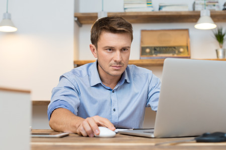 BUSY OFFICE: Portrait of young businessman using laptop in office Stock Photo