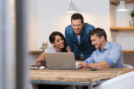 Collega's die samen glimlachen terwijl er door papierwerk in het kantoor Stockfoto