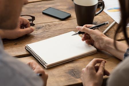 persona escribiendo: Empresario y la mujer tomando nota en la oficina