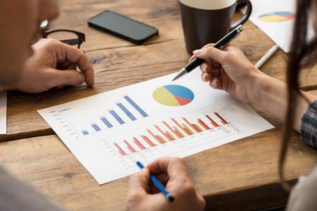 üzlet: Vértes üzletember és a nő megvitatása a tőzsdei dokumentumokat az Office Stock fotó