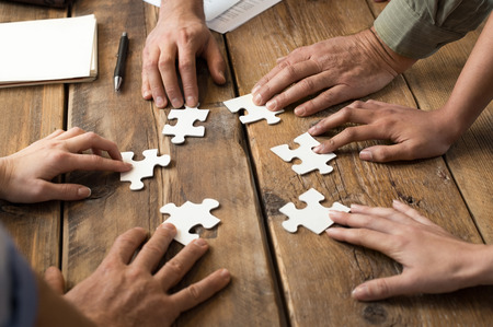work together: Close-up van zakenman en vrouw met puzzelstukken in het kantoor