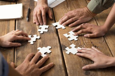 colaboracion: Primer plano de negocios y la mujer con piezas de un rompecabezas en el cargo Foto de archivo