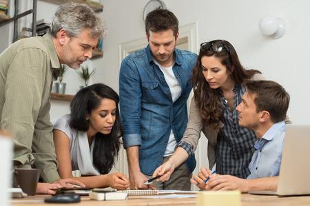 ležérní: Podnikatel a žena dělá diskusi u stolu v kanceláři