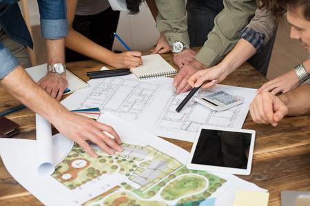 Ondernemers en vrouwen die discussie over blauwdruk in het kantoor Stockfoto