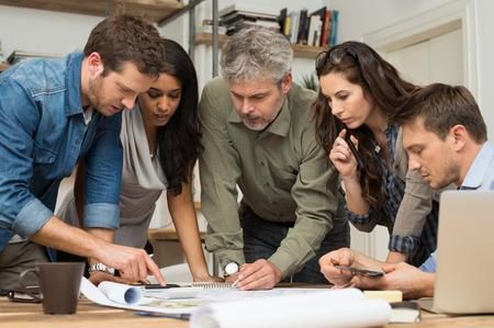 Arquitetos que trabalham e discutem em projetos no escritório