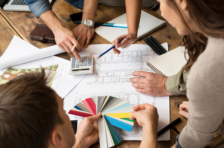 team problems: Architects team discussion on blueprints in office