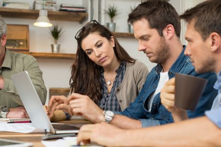 serious: Business people looking at laptop and working together in office