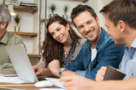 ležérní: Obchodní lidé s úsměvem spolu, když seděl u stolu v kanceláři Reklamní fotografie