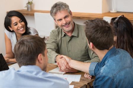 saludo de manos: Sonriente hombre de negocios que buscan el uno al otro y darle la mano a nuevo socio Foto de archivo