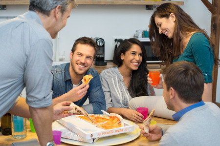 sharing food: Happy friends having dinner together in kitchen