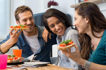 botanas: Jóvenes amigos felices que comen el pan tostado en la cocina