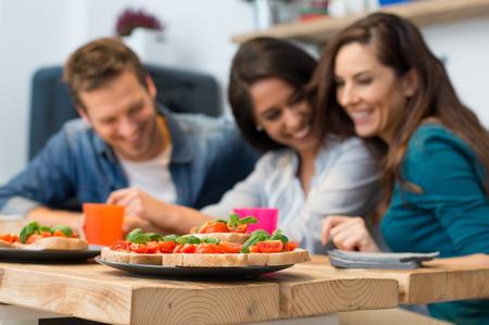 ブルスケッタのクローズ アップはバック グラウンドで人々 とのテーブルで提供しています