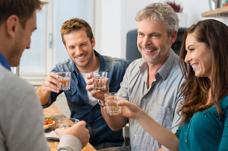 drinking alcohol: Happy friends toasting with wine glasses at home