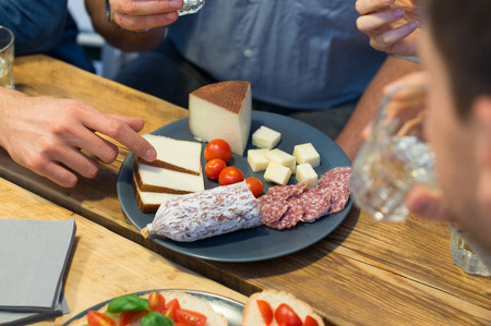 aperitif: Closeup of man picking cheese slice served in plate