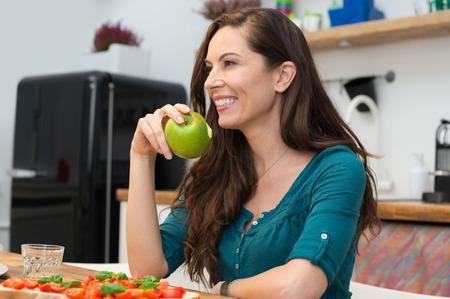 manzana: Retrato de mujer joven comer manzana verde en la cocina Foto de archivo
