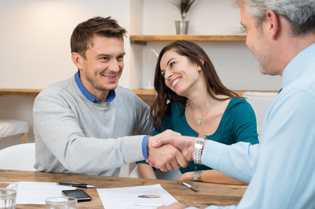 dandose la mano: Feliz pareja joven estrechando la mano de un acuerdo financiero Foto de archivo