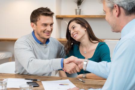 Gelukkig jong paar handen schudden voor een financiële overeenkomst