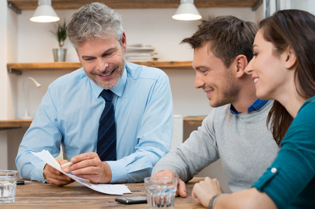 business  deal: Young couple consulting financial agent for new future projects Stock Photo