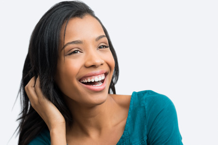 happy black woman: Closeup of young african woman smiling with hand in hair