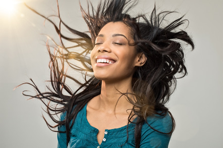 black women hair: Closeup of smiling young woman blowing her hair in the wind Stock Photo