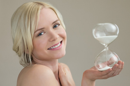 ageing: Beauty portrait of beautiful caucasian woman holding hour glass sand timer