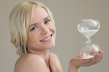 reloj de arena: Retrato de la belleza de la hermosa mujer caucásica sosteniendo horas reloj de arena de cristal