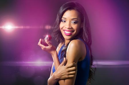 pretty woman: Mooie jonge vrouw in blauwe jurk bedrijf parfumfles