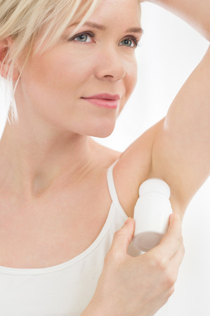 Closeup of young woman applying deodorant to her armpit Stock Photo