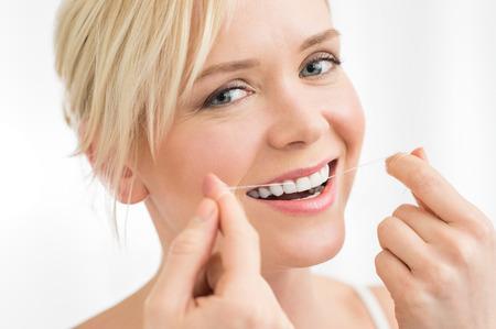 Portrait de jeune femme soie dentaire ses dents avec la soie dentaire regardant la caméra Banque d'images
