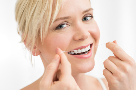 dentaire: Portrait de jeune femme soie dentaire ses dents avec la soie dentaire regardant la caméra Banque d'images