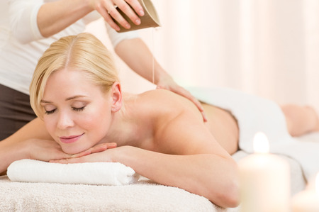 massage oil: Spa therapist pouring massage oil on young woman back at spa Stock Photo