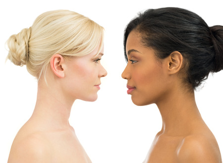 comparisons: Portrait of beautiful african and caucasian women staring at each other isolated on white background Stock Photo