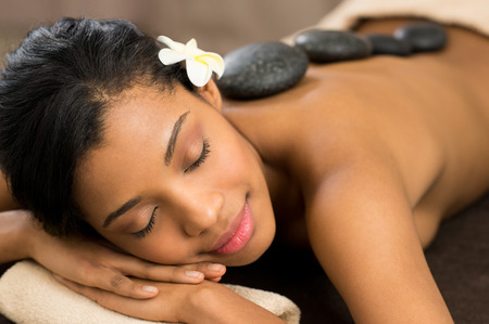 mujeres negras: Joven y bella mujer con los ojos cerrados recibiendo masaje con piedras calientes en el salón del balneario