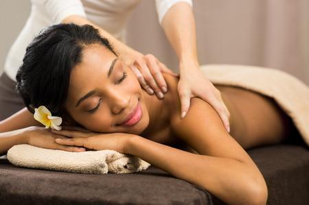 Primer de la mujer africana feliz de recibir masaje de espalda en el spa salón