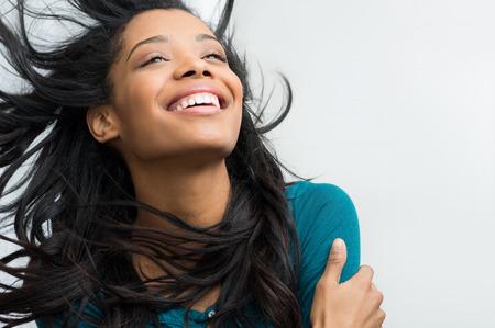 Close-up van lachende jonge vrouw met haar in de wind Stockfoto