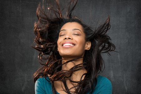 Closeup of smiling young african woman with wind in the hair