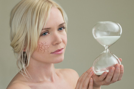 Beauty portrait of young woman holding hour glass sand timer, aging process concept Imagens