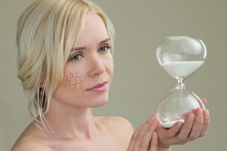 mujer bonita: Retrato de la belleza de la mujer joven que sostiene hora reloj de arena de cristal, el envejecimiento concepto del proceso