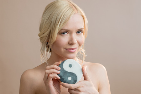 Beauty portrait of beautiful young woman holding yin yang symbol Reklamní fotografie