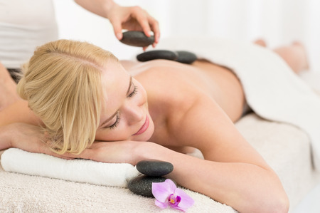 massage stones: Beautiful young woman receiving hot stone massage at salon spa