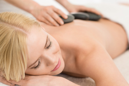 lastone: Beautiful young woman receiving hot stone massage