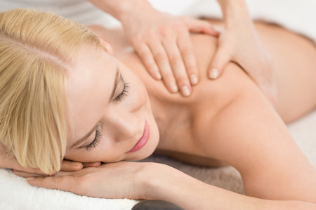 laying on back: Closeup of happy young woman receiving massage at salon spa
