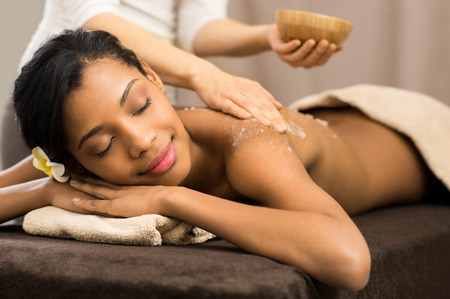 women body: Spa therapist applying scrub salt on young woman back at salon  spa Stock Photo