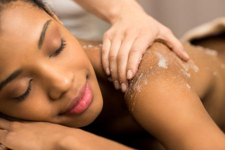 Spa therapist applying massage salt on young woman back at spa photo
